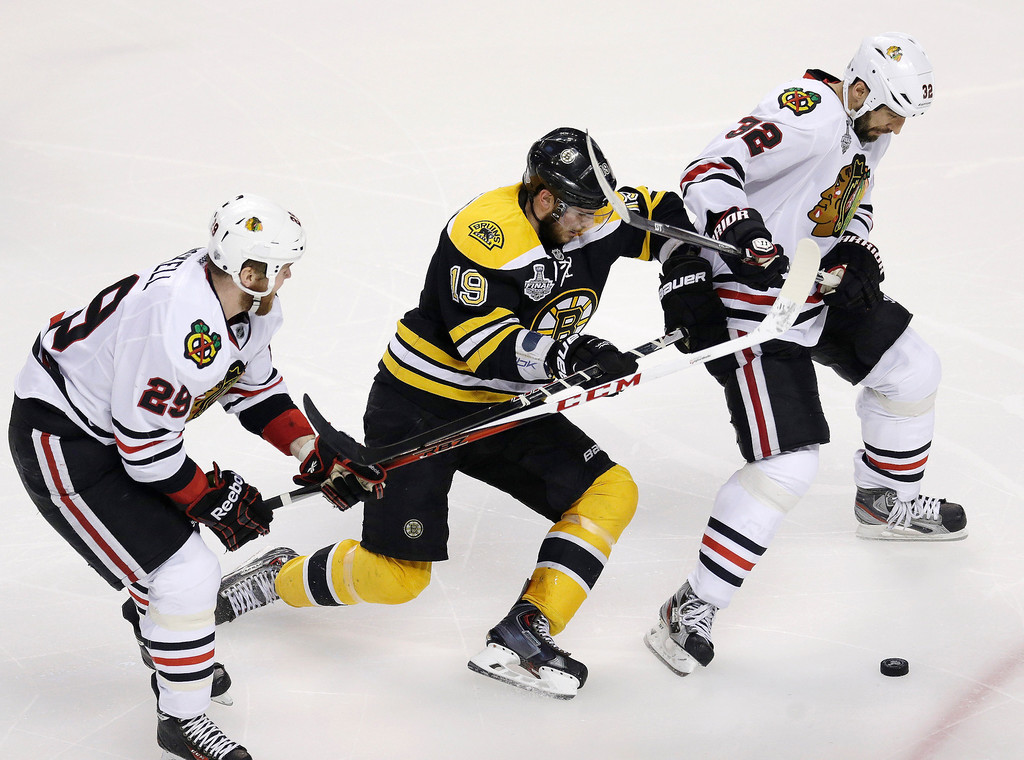 . Boston Bruins center Tyler Seguin (19) pursues the puck between Chicago Blackhawks left wing Bryan Bickell (29) and Blackhawks defenseman Michal Rozsival (32), of the Czech Republic, during the third period in Game 3 of the NHL hockey Stanley Cup Finals in Boston, Monday, June 17, 2013. (AP Photo/Charles Krupa)