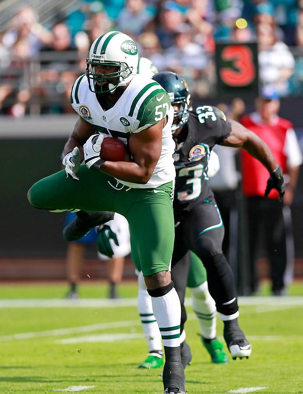 . New York Jets inside linebacker Bart Scott, left, intercepts a pass in front of Jacksonville Jaguars fullback Greg B. Jones (33) during the first half of an NFL football game, Sunday, Dec. 9, 2012, in Jacksonville, Fla. (AP Photo/John Raoux)