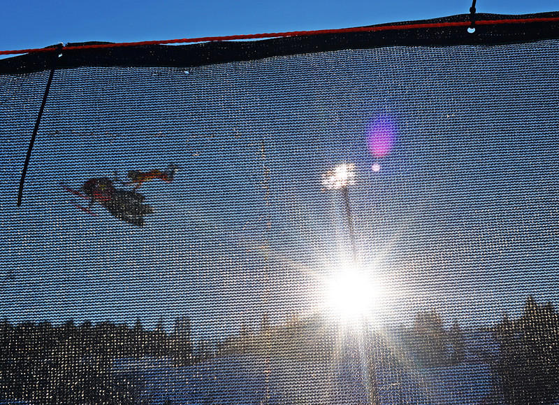 . Colten Moore, seen through a safety fence, practice for the Snowmobile Freestyle during the Winter X Games in Aspen, January, 23 2014. A year ago, Colten Moore\'s brother Caleb Moore passed away a week after crashing during the Snowmobile Freestyle competition at the 2013 Winter X Games in Aspen. (Photo by RJ Sangosti/The Denver Post)