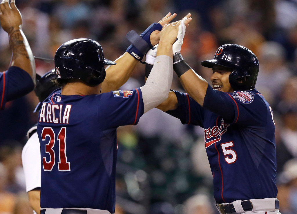 . Minnesota Twins\' Eduardo Escobar (5) is congratulated by teammate Oswaldo Arcia after his three-run home run during the eighth inning of a baseball game against the Detroit Tigers in Detroit, Saturday, Sept. 27, 2014. (AP Photo/Carlos Osorio)