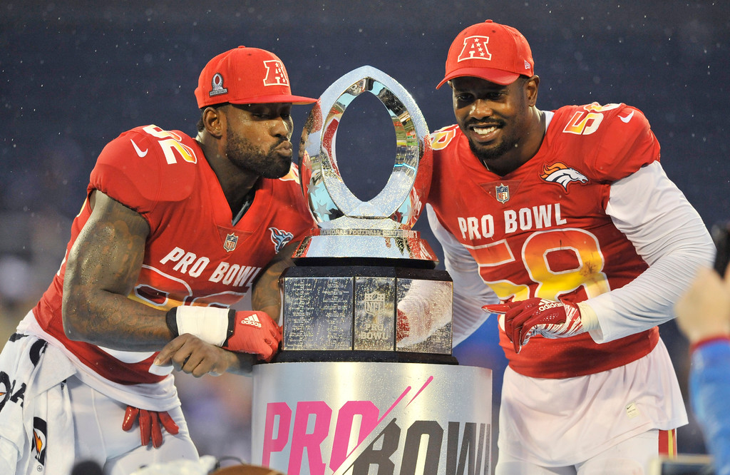 . AFC linebacker Von Miller (58), of the Denver Broncos and tight end Delanie Walker (82), of the Tennessee Titans, pose with the NFL Pro Bowl trophy after defeating the AFC 24-23, in Orlando, Fla., Sunday, Jan. 28, 2018. (AP Photo/Steve Nesius)