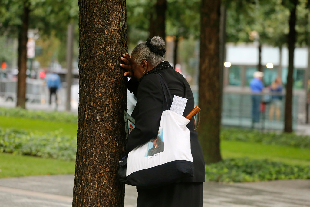 . A woman weeps by herself as she leans against a tree during a ceremony marking the 17th anniversary of the terrorist attacks on the United States. Tuesday, Sept. 11, 2018, at the World Trade Center in New York. (AP Photo/Mark Lennihan)