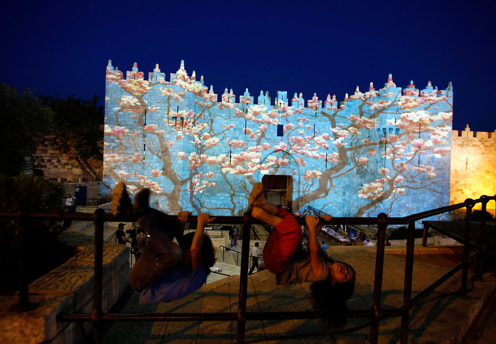 """. Children play in front of Damascus gate outside Jerusalem\'s Old City as it is projected with images during the \""""Jerusalem Light 2013\"""" Festival June 5, 2013. The festival opened on Wednesday night and will run for a week in the Old City of Jerusalem, hosting Israeli and international artists who will display their installations throughout the week. REUTERS/Ammar Awad"""