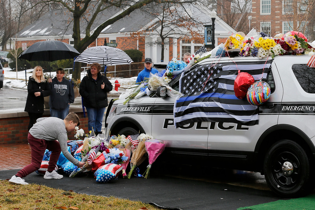 . Mourners gather and leave flowers on a police cruiser parked in front of City Hall in Westerville, Ohio, on Sunday, Feb. 11, 2018. Westerville police officers Anthony Morelli and Eric Joering were killed in the line of duty Saturday when a suspect opened fire on them as they responded to a call at a residence. (Sam Greene/The Cincinnati Enquirer via AP)