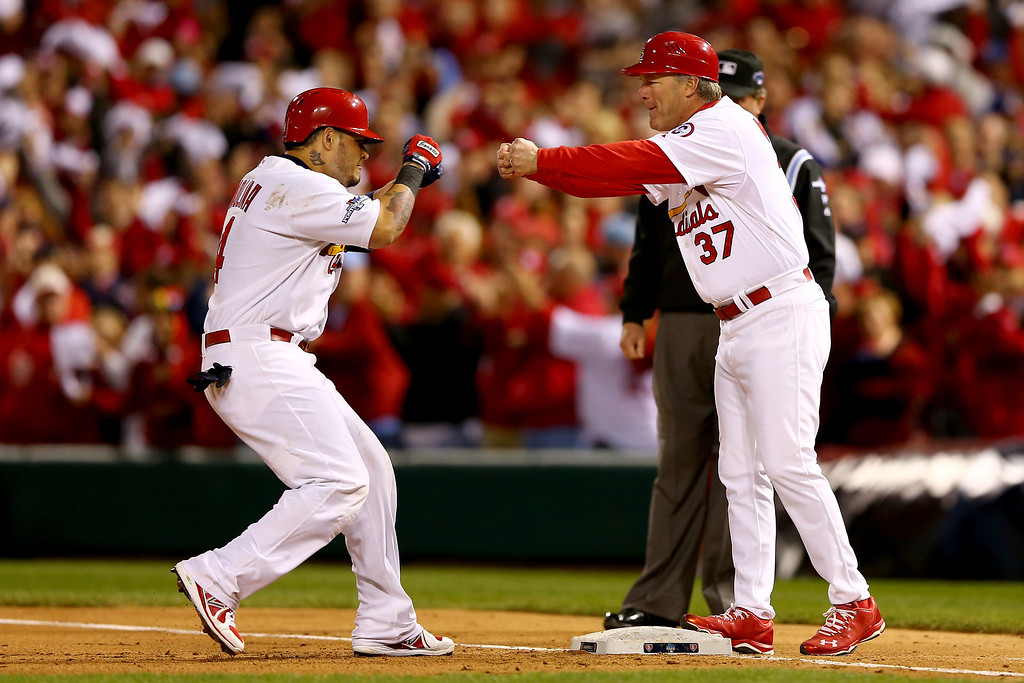 . ST LOUIS, MO - OCTOBER 18:  Yadier Molina #4 of the St. Louis Cardinals celebrates with first base coach first base coach Chris Maloney #37 after Molina hits a RBI single in the third inning against the Los Angeles Dodgers in Game Six of the National League Championship Series at Busch Stadium on October 18, 2013 in St Louis, Missouri.  (Photo by Elsa/Getty Images)