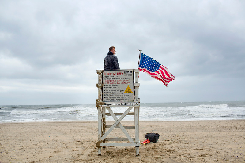 . While strong, gusty winds arrive at the Oceanfront Virginia Beach Lifeguard David Derrick tends to his duties on Friday, July 4, 2014, in Virginia Beach, Va. The storm was expected to bring a lousy July Fourth beach day with it as it moved offshore of the northeast coast. Forecasters did predict a second landfall Saturday evening in New Brunswick and Nova Scotia in Canada. (AP Photo/The Virginian-Pilot, Rich-Joseph Facun)