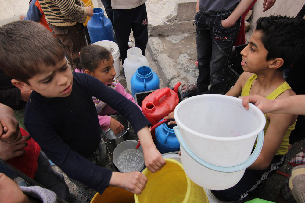 . Children wait to collect water in Aleppo April 2, 2013. Around Syria, water shortages are worsening and supplies are sometimes contaminated, putting children at increased risk of diseases.  REUTERS/Giath Taha