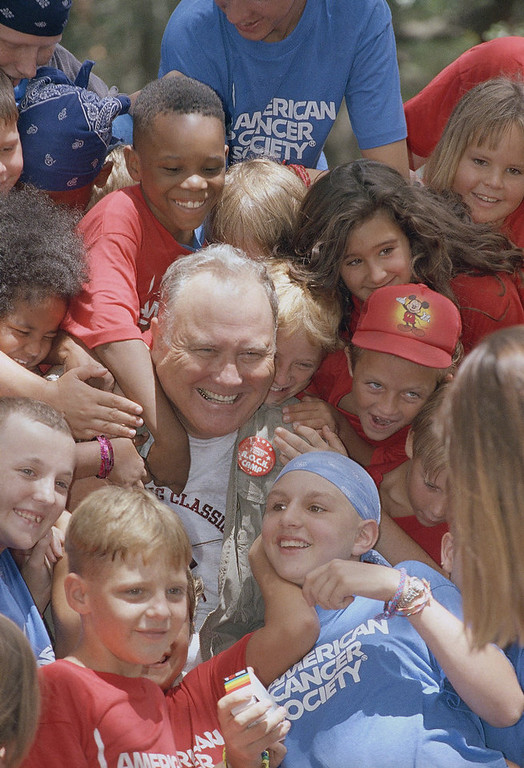. Retired General Norman Schwarzkopf is surrounded by campers during his visit to R.O.C.K., Reaching Out to Cancer Kids Camp on Tuesday, August 3, 1993 in Brandon, Fla. Schwarzkopf visited their barracks and joined in a sing along with the children ages 6 to 18. The cancer stricken kids enjoying the camp this week are from northern Florida. (AP Photo/Peter Cosgrove)