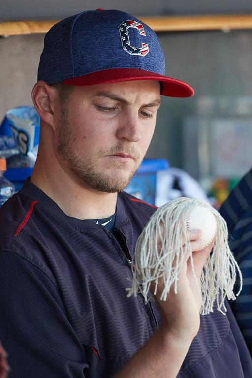 . Cleveland Indians Trevor Bauer adorns a baseball with hair made from the inside of another baseball in the dugout during the sixth inning of a baseball game against the Detroit Tigers in Detroit, Sunday, July 2, 2017. (AP Photo/Rick Osentoski)