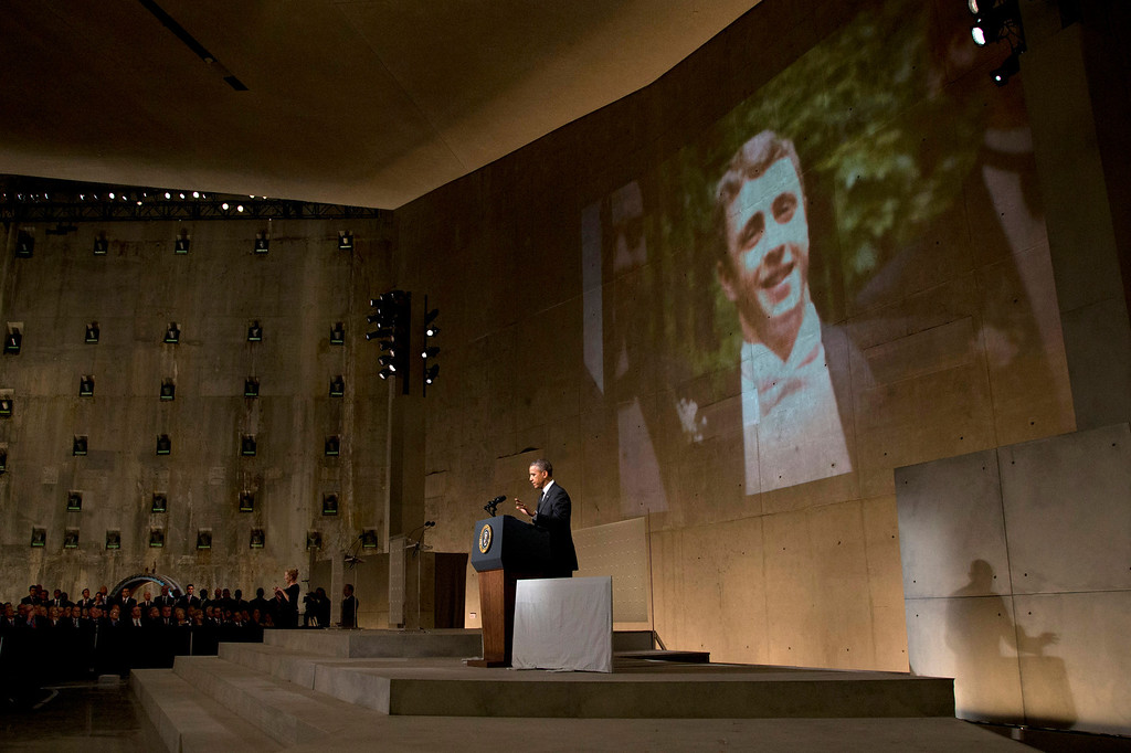 . As the image of Welles Crowther, a victim of the September 11 attacks is displayed behind him, President Barack Obama speaks at the National September 11 Memorial Museum, Thursday, May 15, 2014, in New York. Obama spoke at the dedication in New York for the National September 11 Memorial Museum. He said the museum tells the story of 9/11 so that future generations will never forget.  (AP Photo/Carolyn Kaster)