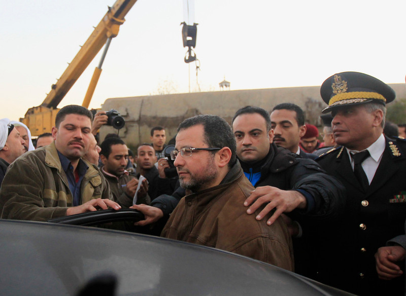 . Egyptian Prime Minister Hisham Kandil (C) visits the site at the wreckage of a military train crash in the Giza neighbourhood of Badrashin, about 40 km (25 miles) west of Cairo, January 15, 2013. A military train carrying young recruits to an army camp derailed in a Cairo suburb on Tuesday, killing 19 people and injuring 107, Egypt\'s health ministry spokesman said.  REUTERS/Mohamed Abd El Ghany