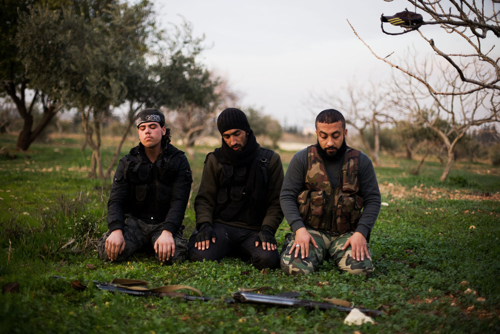Description of . FSA fighters pray after an attack on a Military Academy in Tal Sheer village, north of Aleppo province, Syria, Thursday, Dec 13, 2012. (AP Photo / Manu Brabo)
