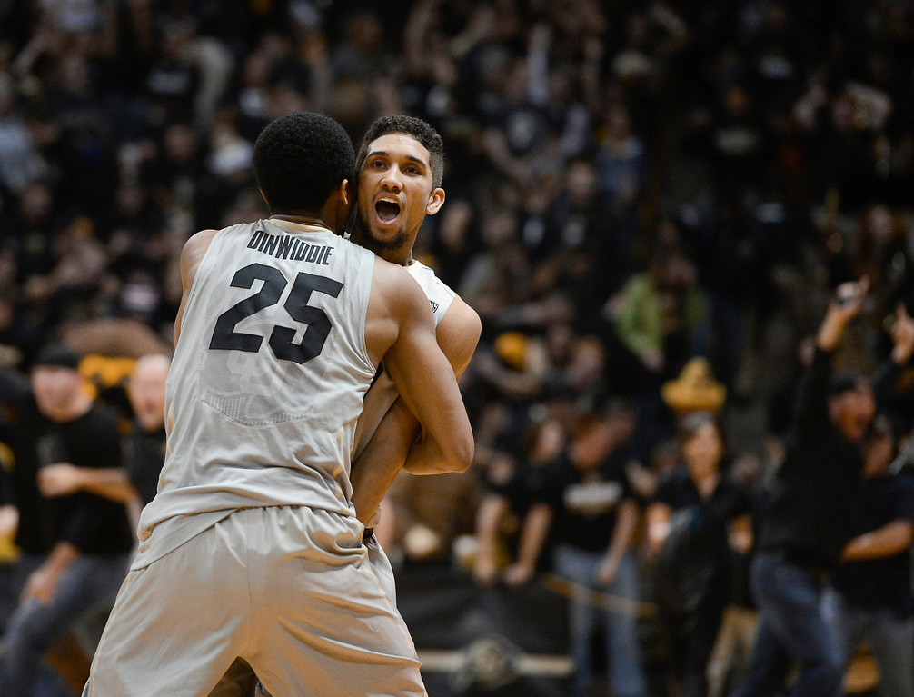 . Colorado University guard, Askia Booker, right, stands in place, shocked that he sunk a three-pointer on the last shot of the game to win against the Kansas Jayhawks 75-72 at the Coors Events Center in Boulder Colorado Saturday afternoon, December 07, 2013. CU teammate, Spencer Dinwiddie, left, charges Booker to celebrate.  (Photo By Andy Cross/The Denver Post)