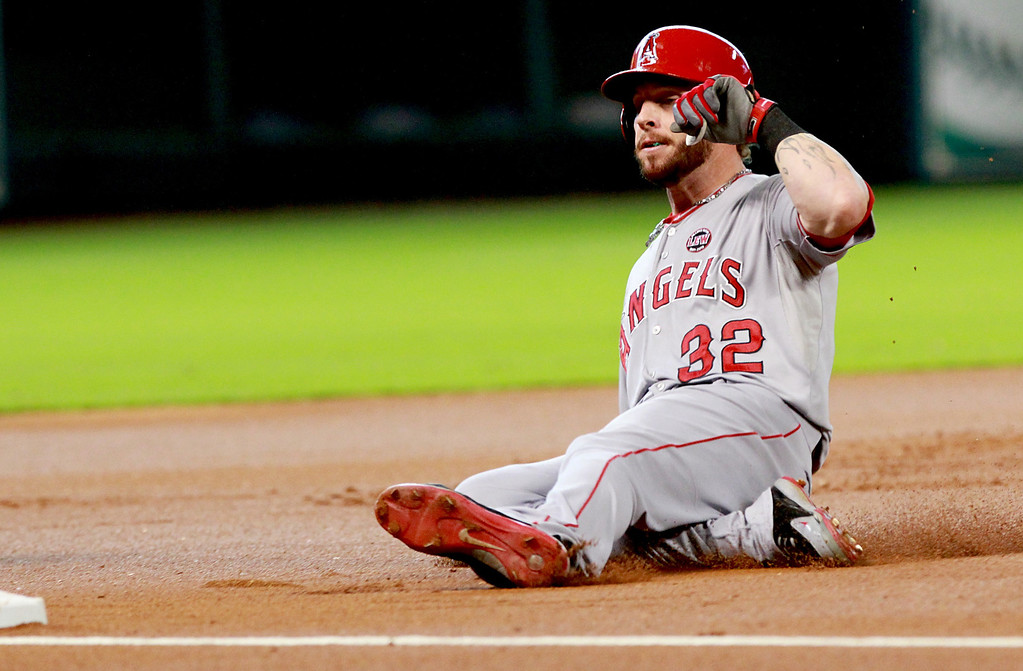 . HOUSTON, TX- SEPTEMBER 15: Josh Hamilton #32 of the Los Angeles Angels slides into third scoring Mike Trout #27 of the Los Angeles Angels of Anaheim against the Houston Astros in the first inning on September 15, 2013 at Minute Maid Park in Houston, Texas. (Photo by Thomas B. Shea/Getty Images)