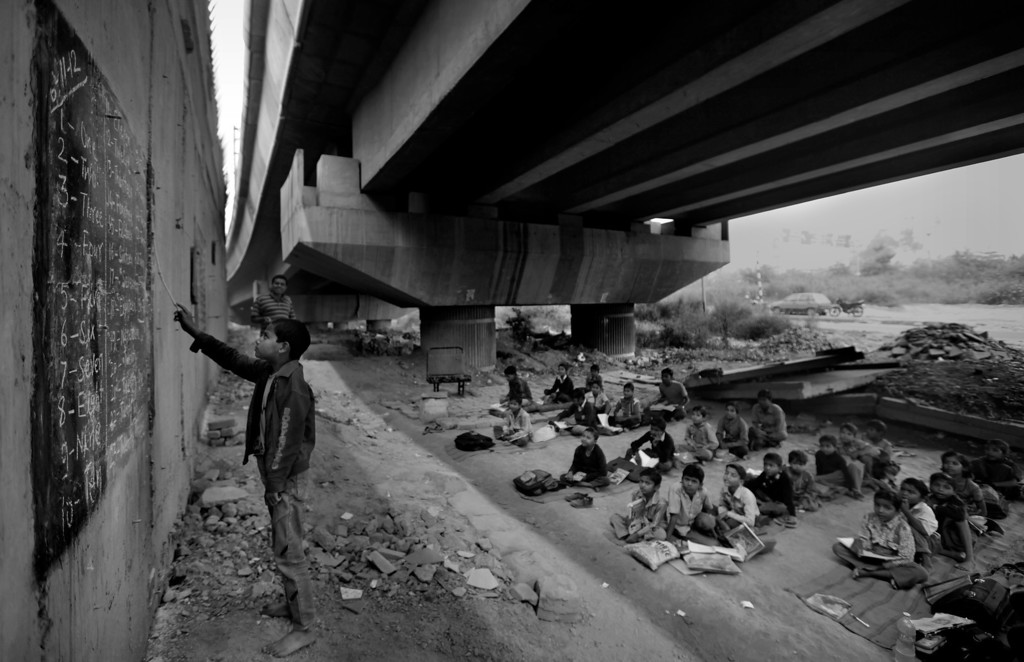 . In this Nov. 7, 2012 photo, an underprivileged Indian child reads from a black board, painted on a building wall, at a free school run under a metro bridge in New Delhi, India. This photo was one in a series of images by Associated Press photographer Altaf Qadri that received an honorable mention in the World Press Photo 2013 photo contest for the Contemporary Issues series category. (AP Photo/Altaf Qadri, File)