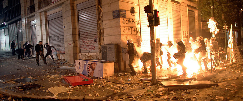 ". Demonstrators throw pfire bombs to riot police during violent protests in central Athens February 12, 2012. Thousands of demonstrators clashed with police as the Greek parliament prepared to vote on a new and deeply unpopular EU/IMF austerity deal, to secure a 130 billion euro bailout, aimed at saving Greece from bankruptcy and what Prime Minister Lucas Papademos warned would be ""uncontrollable economic chaos\"".  (Photo by Milos Bicanski/Getty Images)"