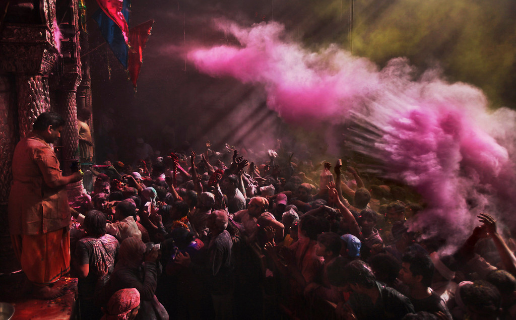 . Hindu devotees throw colored powder on each other inside Banke Bihari temple during Holi festival celebrations in Vrindavan, India, Tuesday, March 26, 2013. Holi, the festival of colors celebrates the arrival of spring among other things. (AP Photo/Altaf Qadri)