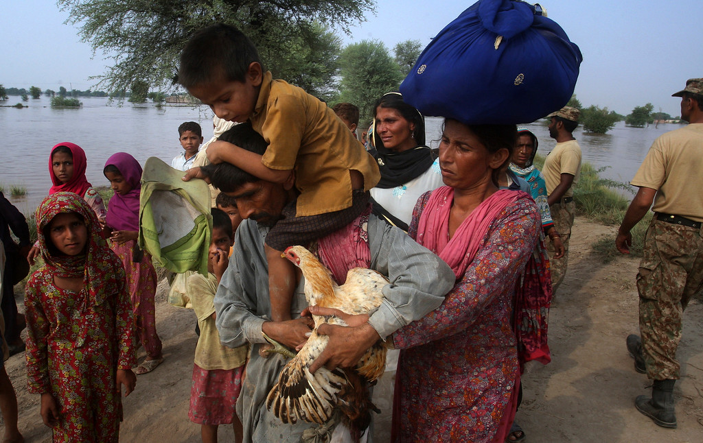 . A Pakistani man carries his son and a rooster are evacuated by army troops as families flee from a flooded area of Jhang district, 260 kilometers (161 miles) northwest of Lahore, Pakistan, Wednesday, Sept. 10, 2014. (AP Photo/K.M. Chaudary)