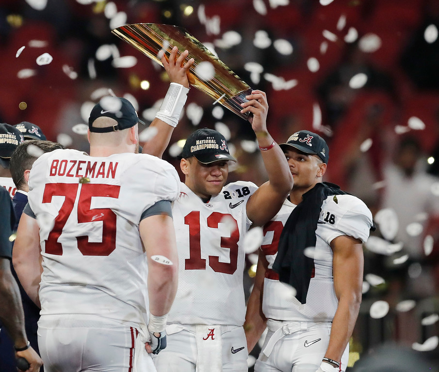 . Alabama\'s Tua Tagovailoa holds up the championship trophy after overtime of the NCAA college football playoff championship game against Georgia Monday, Jan. 8, 2018, in Atlanta. Alabama won 26-23. (AP Photo/David Goldman)