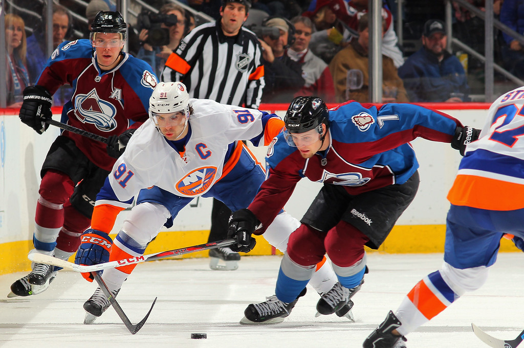 . DENVER, CO - JANUARY 10:  John Tavares #91 of the New York Islanders and John Mitchell #7 of the Colorado Avalanche battle for control of the puck at Pepsi Center on January 10, 2014 in Denver, Colorado.  (Photo by Doug Pensinger/Getty Images)