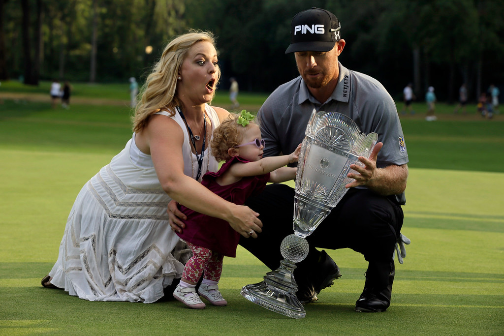 . Zoe Mahan, center, pushes the trophy as her mother Kandi  Mahan, left, grabs her while they pose with Hunter Mahan, husband,  father and winner of The Barclays golf tournament Sunday, Aug. 24, 2014, in Paramus, N.J. (AP Photo/Mel Evans, File)