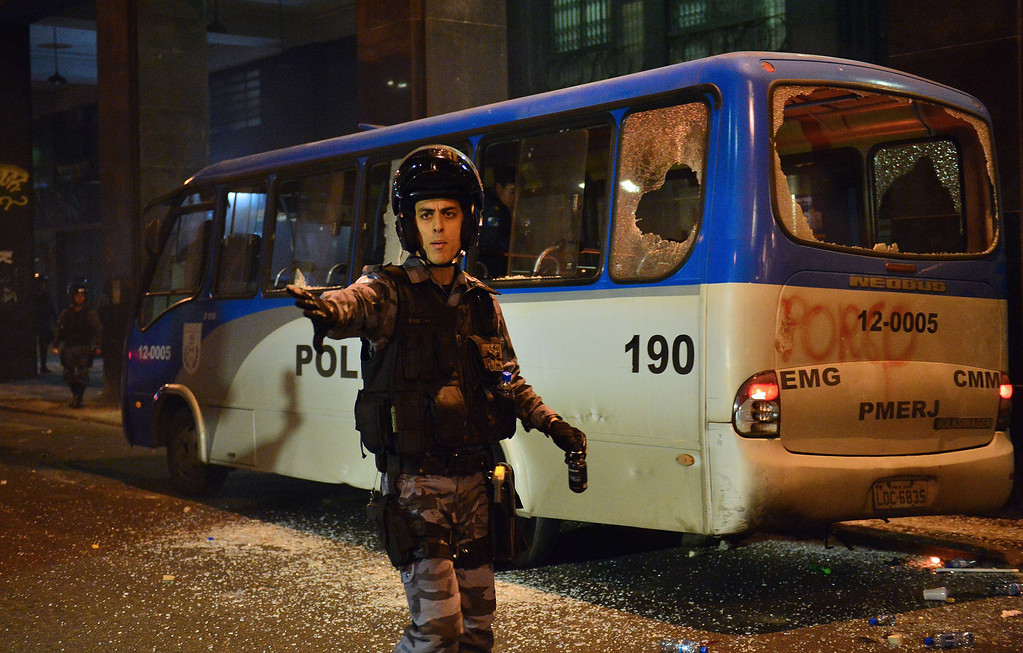 """. A policeman remains next to a damaged police bus during clashes after a protest for the \""""Teachers\' day\"""", on October 15, 2013 in Rio de Janeiro, Brazil. AFP PHOTO / CHRISTOPHE SIMON/AFP/Getty Images"""