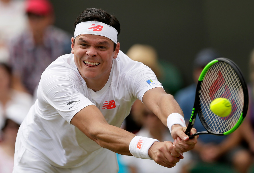 . Milos Raonic of Canada returns the ball to John Millman of Australia during their men\'s singles match on the third day at the Wimbledon Tennis Championships in London, Wednesday July 4, 2018. (AP Photo/Tim Ireland)