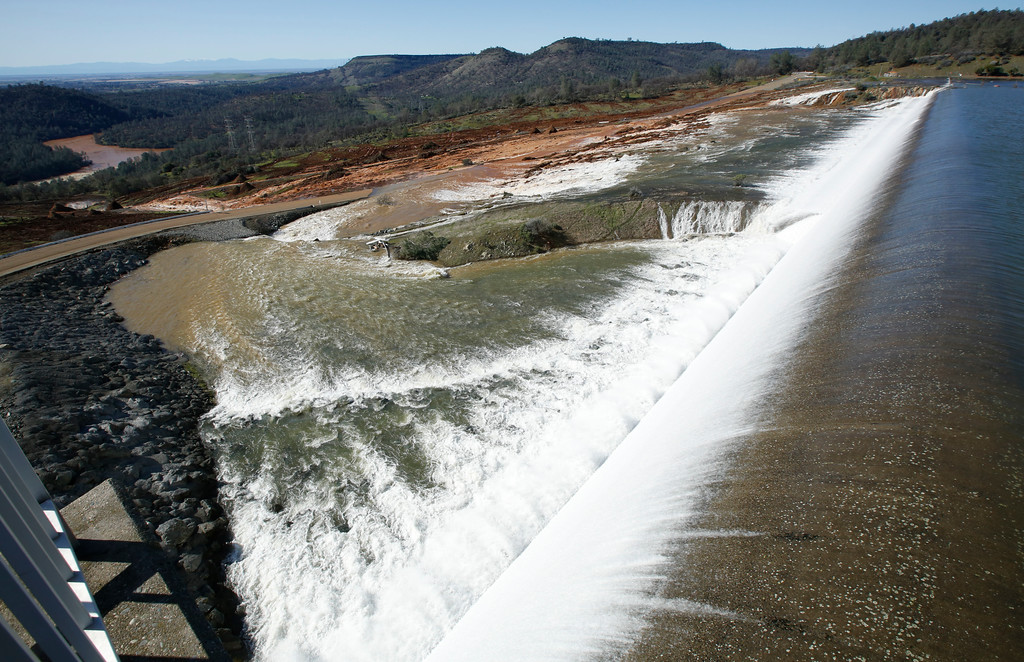 . Water flows over the emergency spillway at Oroville Dam Saturday, Feb. 11, 2017, in Oroville, Calif. Water started flowing over the emergency spillway at the nation\'s tallest dam for the first time Saturday after erosion damaged the Northern California dam\'s main spillway.(AP Photo/Rich Pedroncelli)
