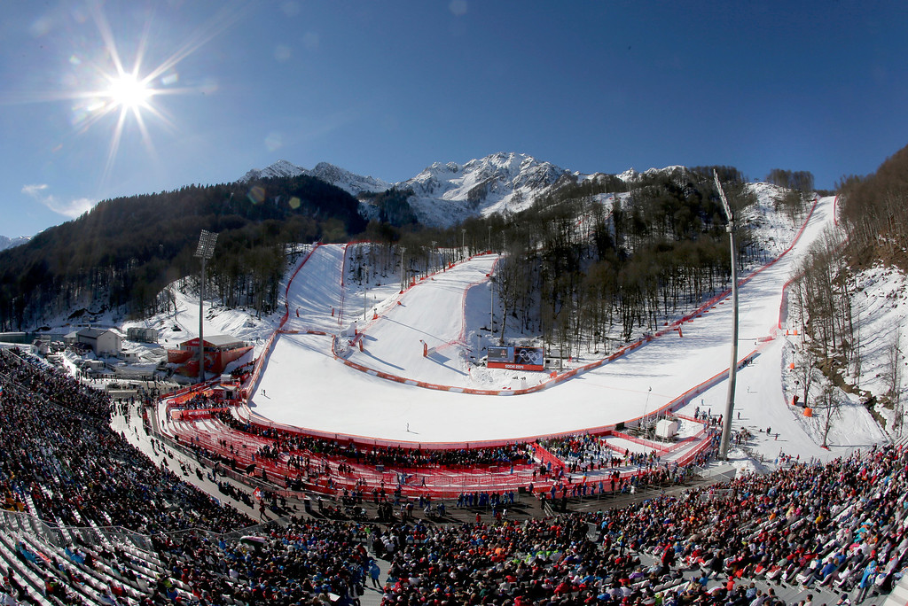 . Fans watch the women\'s downhill competition at the 2014 Winter Olympics, Wednesday, Feb. 12, 2014, in Krasnaya Polyana, Russia. (AP Photo/Charlie Riedel)