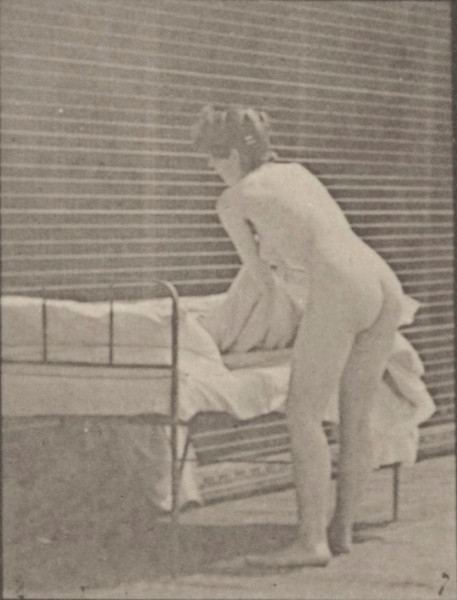 Nude woman making up a bed