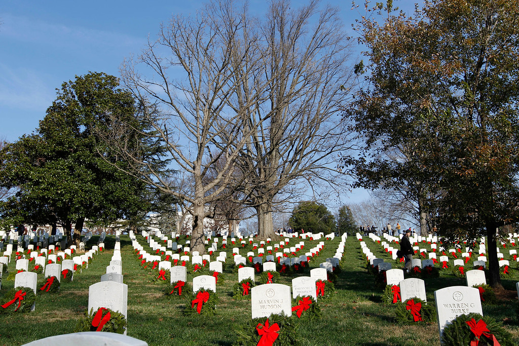 . Volunteers help to place holiday wreaths over the graves of fallen soldiers during Wreaths Across America Day  at Arlington Cemetery on Saturday Dec. 10, 2011. (AP Photo/Jose Luis Magana)