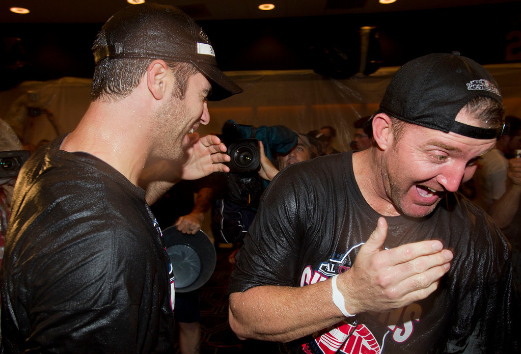 . Minnesota Twins\' Joe Mauer, left, and Jim Thome celebrate after clinching the American League Central division Wednesday, Sept. 22, 2010, in Minneapolis. The Twins beat the Indians 6-4 and the White Sox lost to the Athletics 7-2 to clinch the title. (AP Photo/Jim Mone)