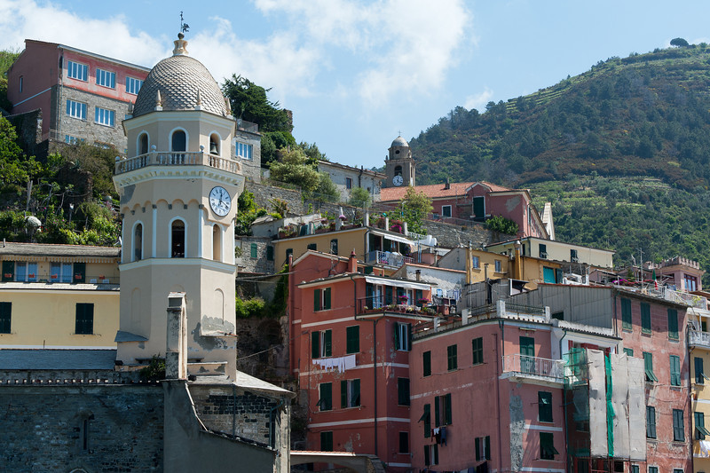 The clock tower in Vernazza Harbor and buildings in Cinque Terre, Italy