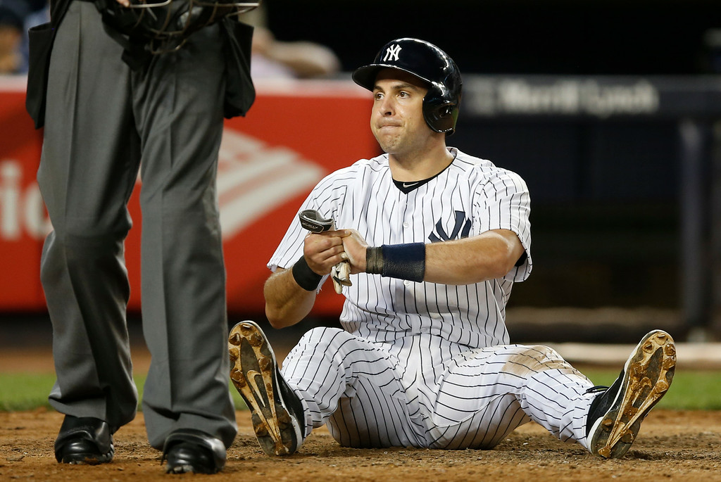 . New York Yankees Mark Teixeira sits in the dirt after injuring his left hand sliding home on an eighth-inning play at the plate in the Yankees 5-1 victory over the Detroit Tigers in a baseball game at Yankee Stadium in New York, Wednesday, Aug. 6, 2014.  (AP Photo/Kathy Willens)