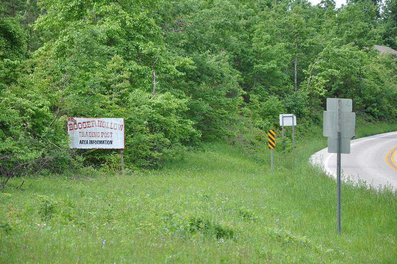 "The sign reads, ""Booger Hollow, Trading Post, Area Information (13 miles up the road)."" Hwy 123."