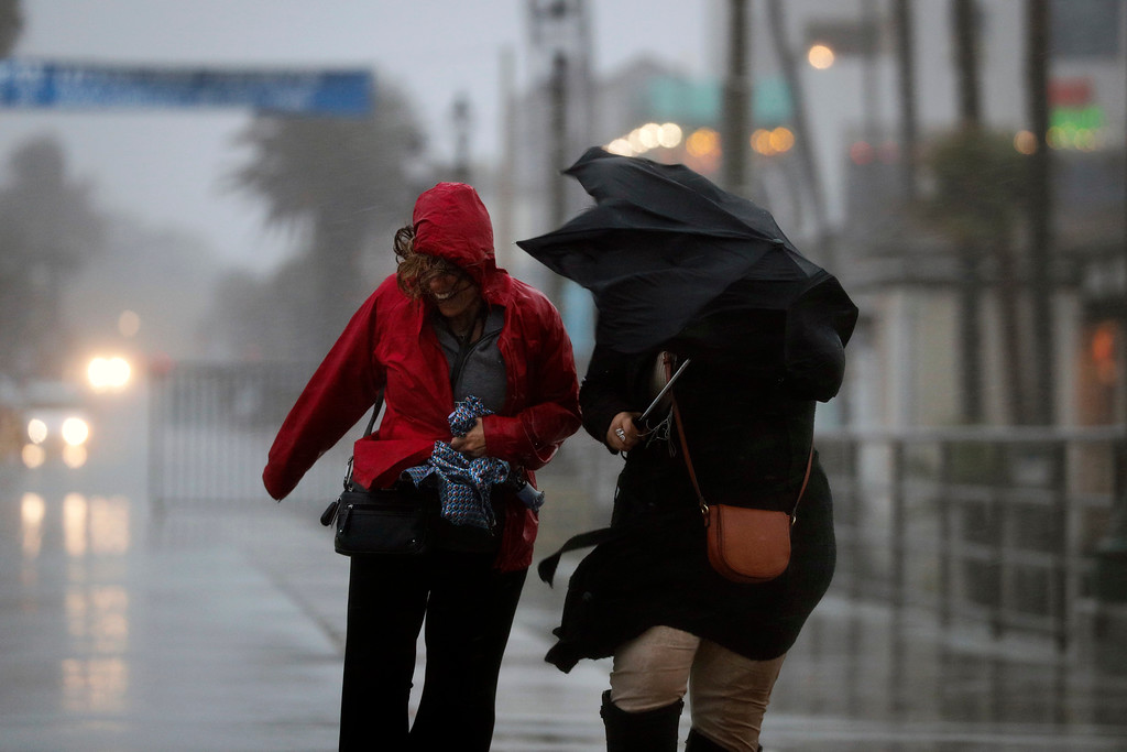 . Rita Maissno, right, and Lara Seltzer make their way through heavy rain and gusty wind as they walk along a pier Friday, Feb. 17, 2017, in Huntington Beach, Calif. A major Pacific storm has unleashed downpours and fierce gusts on Southern California, triggering flash flood warnings and other problems. (AP Photo/Jae C. Hong)
