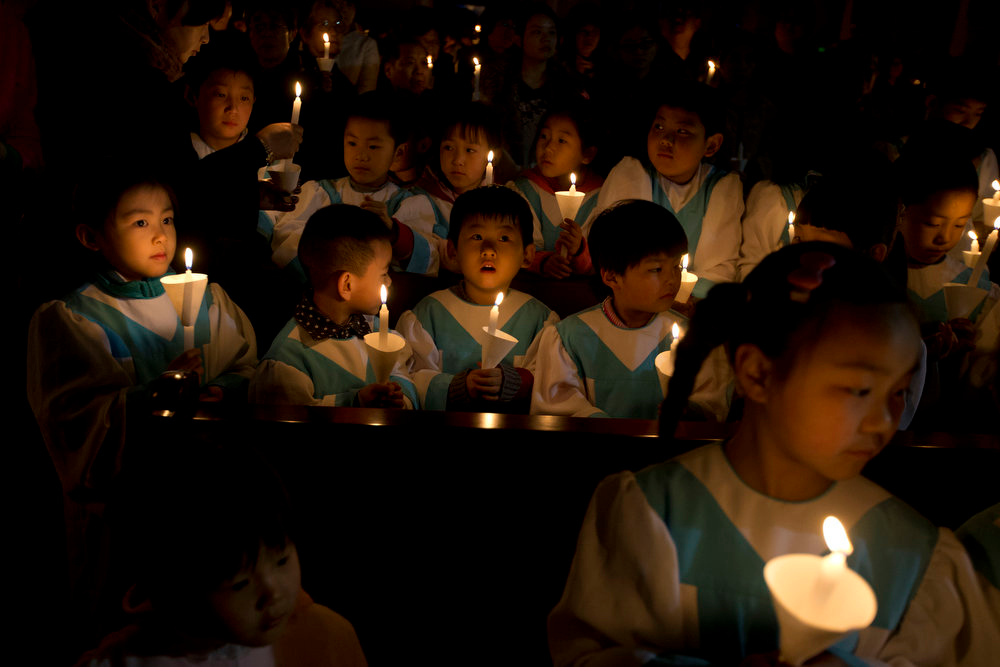Description of . Young children attend a candle light mass on the eve of Easter Sunday at the Southern Cathedral in Beijing, China, Saturday, March 30, 2013. (AP Photo/Ng Han Guan)