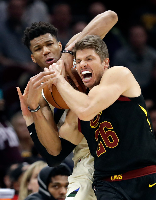 . Milwaukee Bucks\' Giannis Antetokounmpo, back, from Greece, fouls Cleveland Cavaliers\' Kyle Korver in the second half of an NBA basketball game, Monday, March 19, 2018, in Cleveland. The Cavaliers won 124-117. (AP Photo/Tony Dejak)