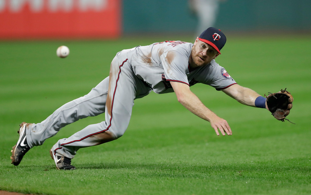 . Minnesota Twins\' Logan Forsythe dives for the ball hit by Cleveland Indians\' Michael Brantley in the sixth inning of a baseball game, Tuesday, Aug. 7, 2018, in Cleveland. Brantley was safe at first base. (AP Photo/Tony Dejak)