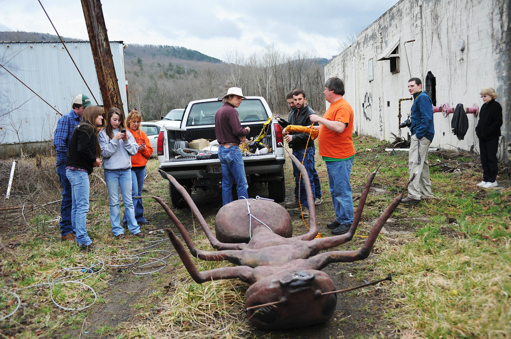 . The group ties a cable around the base of a large ant sculpture to pull up on top of a water tower at the abandoned Stillwater plant on Sunday, March 31, 2013, in Goshen, Va. The ant was a part of an April Fools prank by Mark Cline, who is notorious in the Shenandoah Valley for his annual elaborate sculpture-based pranks, such as Foam Henge.  (AP Photo/The Daily News Leader, Katie Currid)