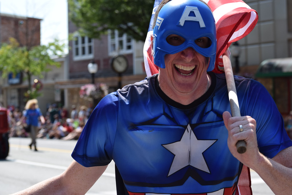 . A parade participant dressed as Captain America high-fives guests as he runs down High Street during the Fourth of July parade Tuesday.--Marian Dennis, Digital First Media
