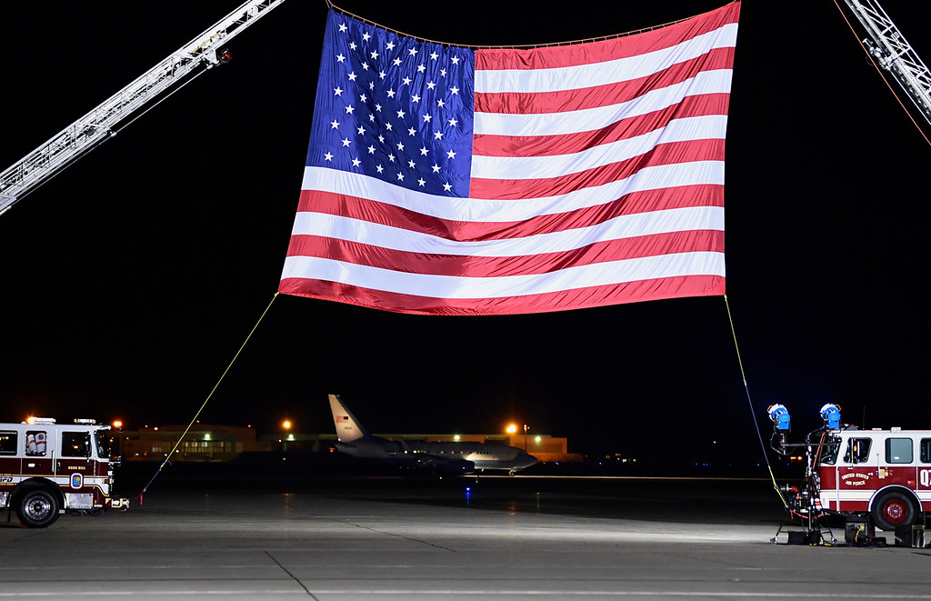 . A U.S. government plane, seen in the background below the flag, carrying three Americans freed from captivity in North Korea arrives at Andrews Air Force Base in Md., Thursday, May 10, 2018. President Donald Trump is on hand to greet them. (AP Photo/Susan Walsh)