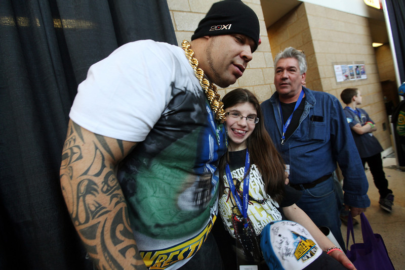 . Brodus Clay, left, poses with Brittany Chamberlan, center, as her father Gary watches at right before the WWE Wrestlemania 29 wrestling event, Sunday, April 7, 2013, in East Rutherford, N.J. (AP Photo/The Record of Bergen County, Chris Pedota)