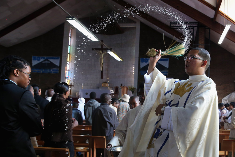 """. Father Sebastian Rossouw O.M.I. sprinkes holy water on congregants during Easter services at Regina Mundi Catholic Church in the Soweto area March 31, 2013 in Johannesburg, South Africa. A central gathering place during he anti-apartheid struggle, the church held prayers for former South African President Nelson Mandela, 94, who is in the hospital for the third time since December with lung problems. Referring to Mandela by clan name, Madiba, President Jacob Zuma said, \""""We appeal to the people of South Africa and the world to pray for our beloved Madiba and his family and to keep them in their thoughts.\"""" Mandela\'s lungs were damaged when he contracted tuberculosis during his 27 years in the infamous Robben Island prison. Mandela became the nation\'s first democratically elected president in 1994 following the end of apartheid.  (Photo by Chip Somodevilla/Getty Images)"""