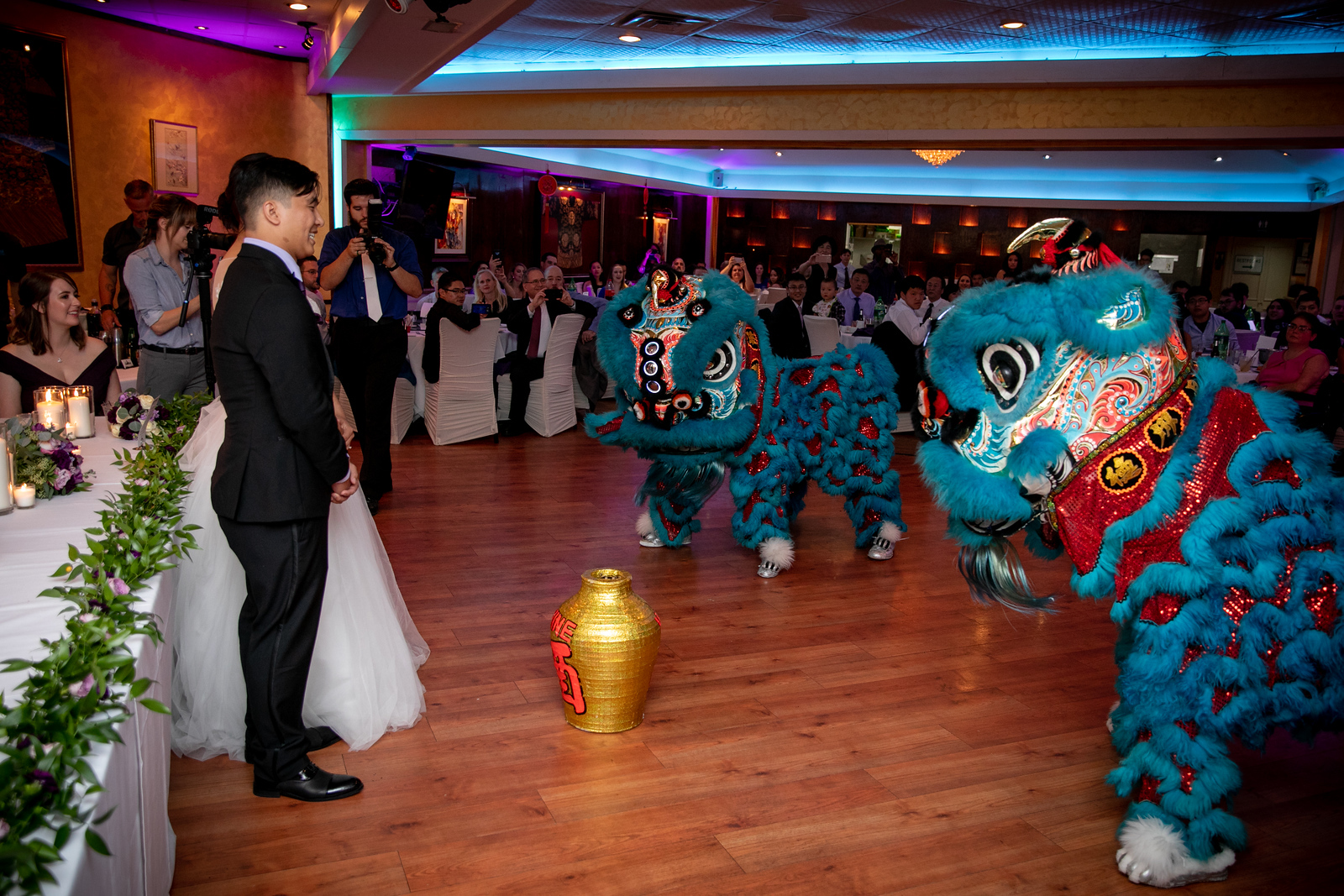A bride and groom watching dragon dancers open up their wedding night reception ceremonies