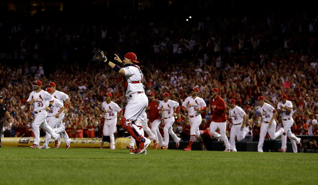 . St. Louis Cardinals catcher Yadier Molina raises his arms in celebration after the Cardinals\' 7-0 win over the Chicago Cubs in a baseball game to clinch the NL Central title Friday, Sept. 27, 2013, in St. Louis. (AP Photo/Jeff Roberson)