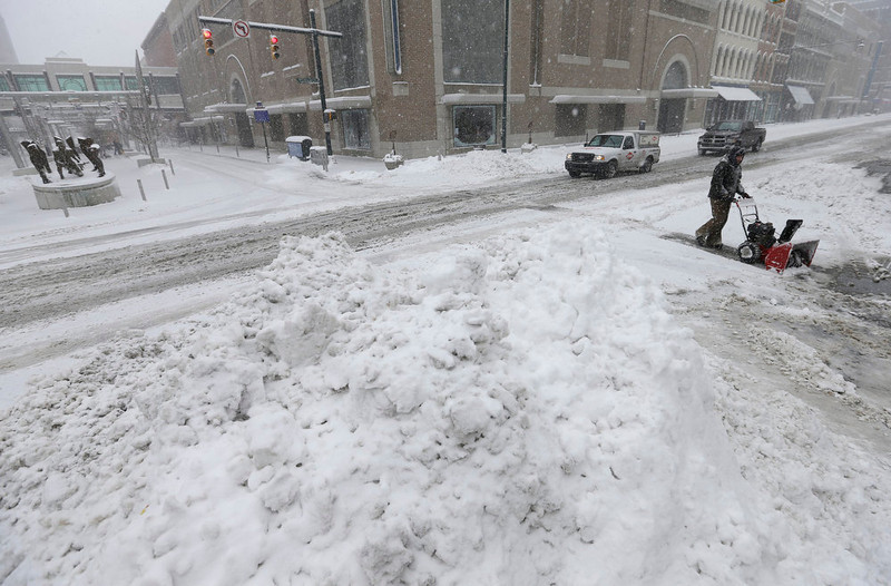 . A worker uses a snow blower to remove snow as motorist passes by in downtown Indianapolis Wednesday, Dec. 26, 2012. The blizzard warning issued the day before by National Weather Service came to fruition in the region Wednesday as winds picked up and snow began falling in earnest before dawn. (AP Photo/Darron Cummings)