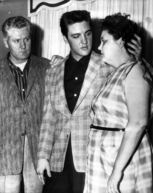 . Elvis Presley, 23-year-old rock and roll singer and movie actor, comforts his mother Gladys as his father, Vernon E., looks on. The scene took place last night when photographers were admitted to the Presleys\' Memphis home on the eve of Elvis\' induction into the army.