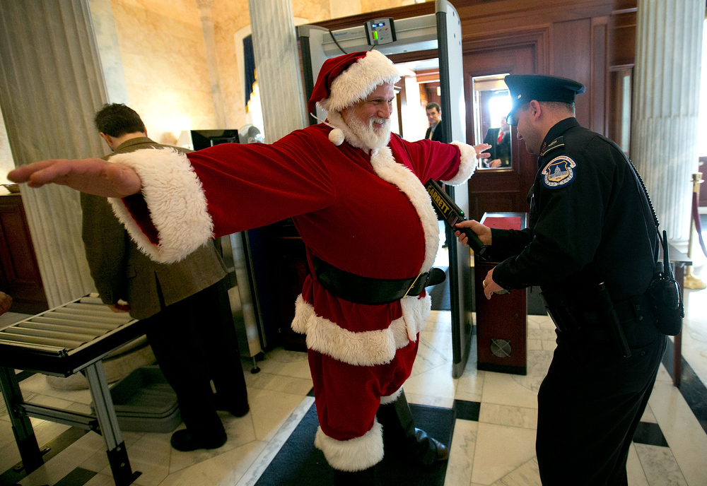 Description of . Capitol Hill police check an unidentified man dressed as Santa Claus with a metal detector as he enters the U.S. Capitol on his way to Speaker of the House John Boehner's office on December 12, 2012 in Washington, DC. The man was working with the group Catholics United, and wanted to urge Speaker of the House John Boehner to pass pending