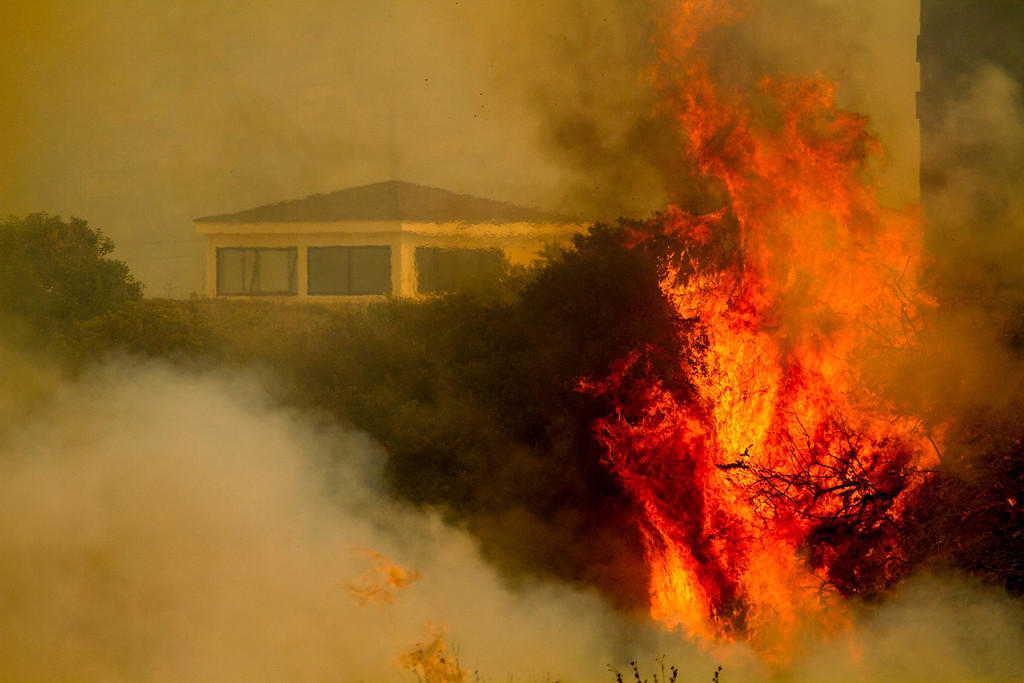 . Flame and smoke rise from The Naval Base at Point Mugu, Calif., Friday, May 3, 2013. The 15 1/2-square-mile blaze was only 10 percent contained on Friday, and the work of more than 900 firefighters, aided by air tankers, was just beginning. (AP Photo/Ringo H.W. Chiu)